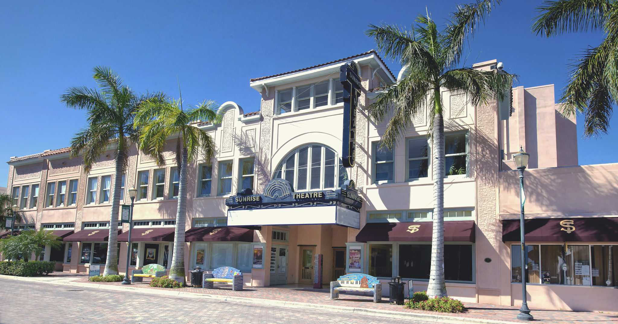 The front of the sunrise theatre bukilding with the Sunrise marquee in front and palm trees in front of the building.